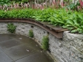 tuinontwerp met stapelmuur muurplantjes en houten zitrand