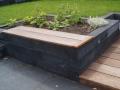 Terras-met-verhoogde-border-en-houten-zitrand